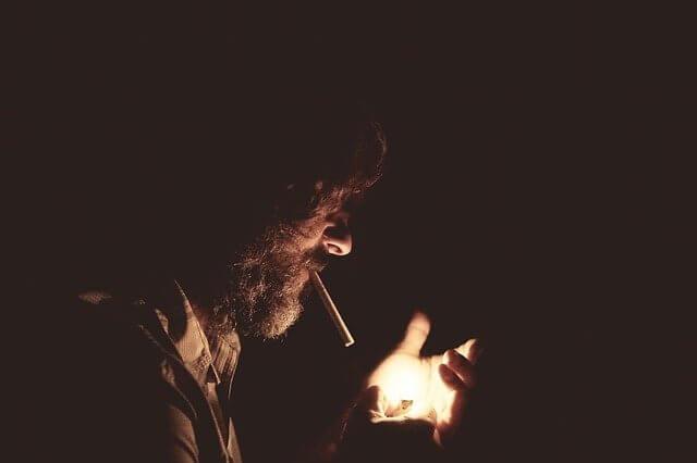 Mies polttaa tupakkaa